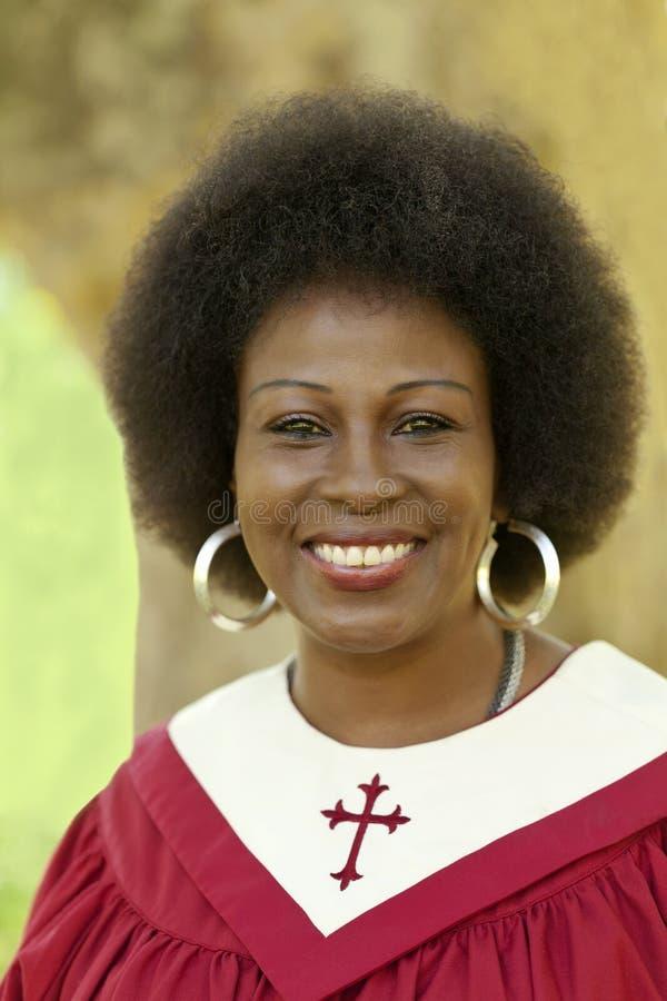 Frau von mittlerem Alter, die draußen rote Kirchen-Robe lächelt stockfoto