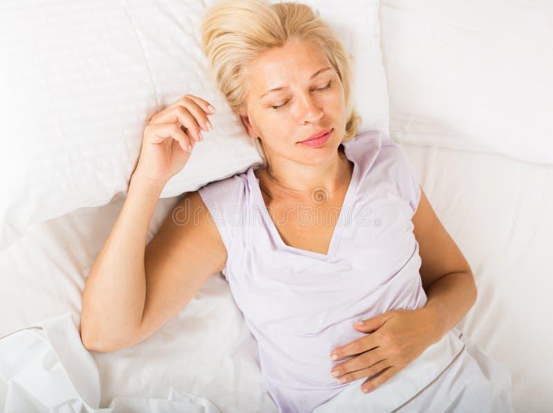 Frau von mittlerem Alter, die im Bett schläft stockfotos