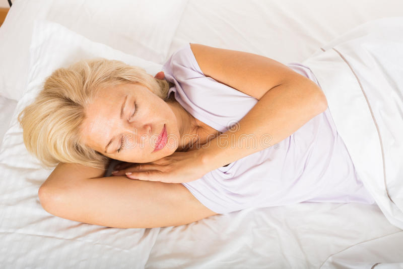 Frau von mittlerem Alter, die im Bett schläft lizenzfreie stockbilder