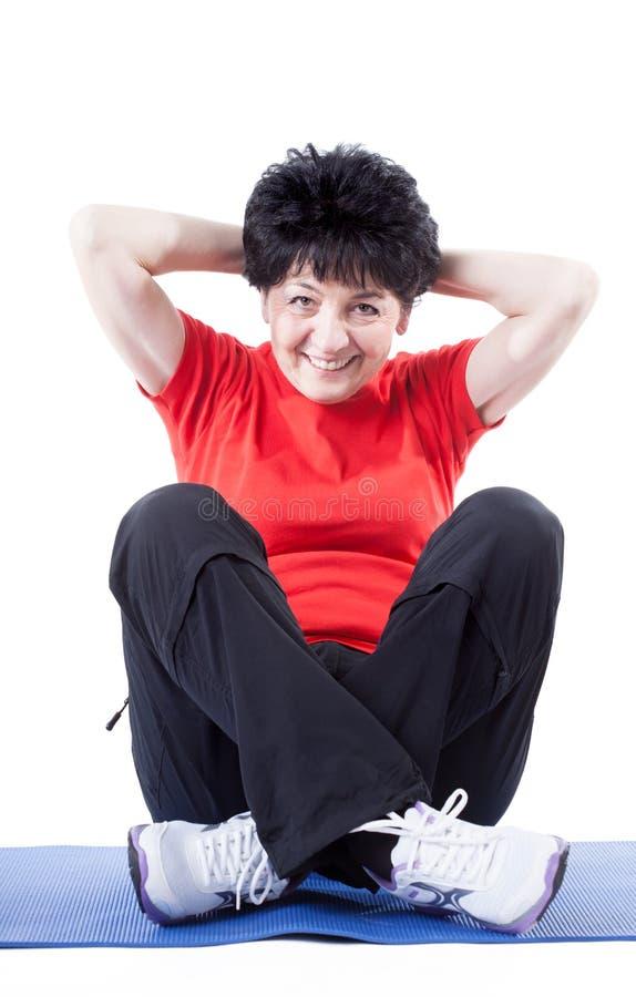 Frau von mittlerem Alter, die SitzenUPS tut lizenzfreie stockfotos