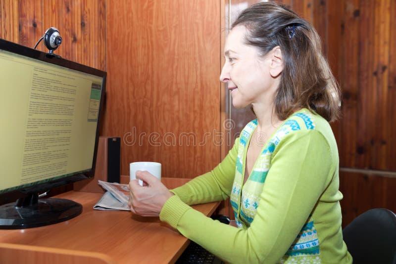 Frau von mittlerem Alter nahe Heimcomputer lizenzfreie stockfotos