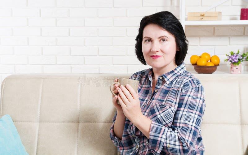 Frau von mittlerem Alter sitzt auf Couch und genießt köstliches heißes Getränk nach der Arbeit des harter Tages lizenzfreie stockbilder