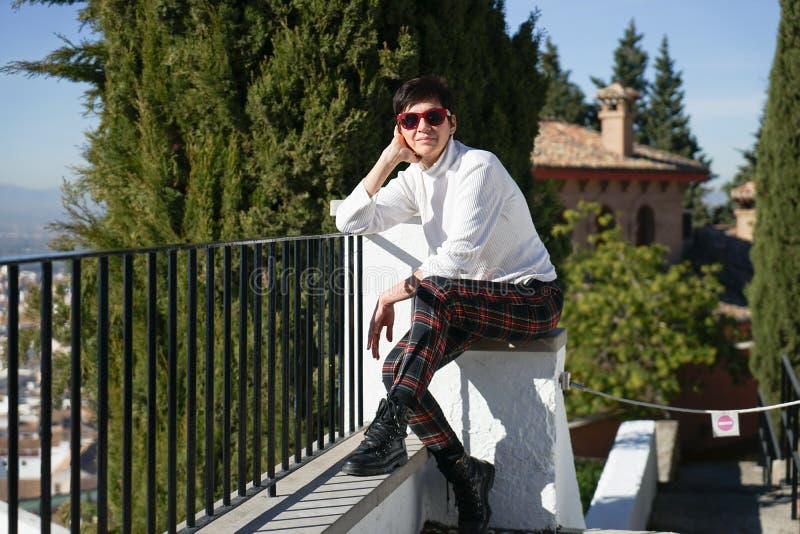 Frau von mittlerem Alter, welche die Ansichten von Granada genießt stockfoto