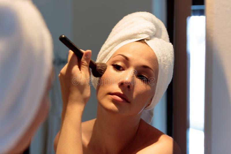 Frau vor dem Spiegel, der auf Make-up sich setzt, bevor es nachts erlischt lizenzfreie stockbilder