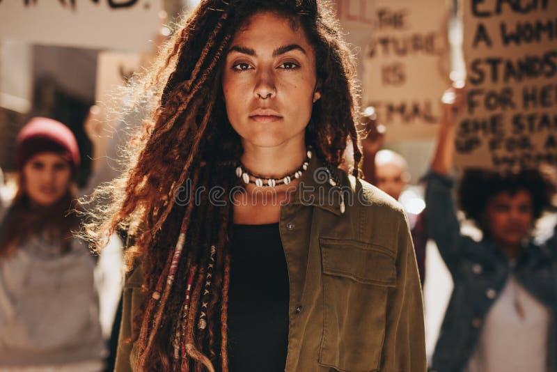 Frau vor Demonstranten auf Straße stockfoto