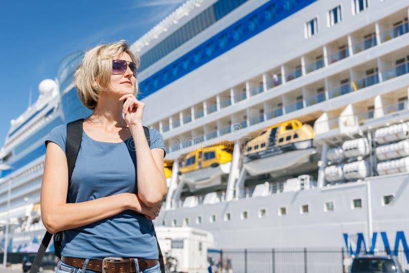 Frau vor Kreuzfahrtschiff lizenzfreie stockfotografie