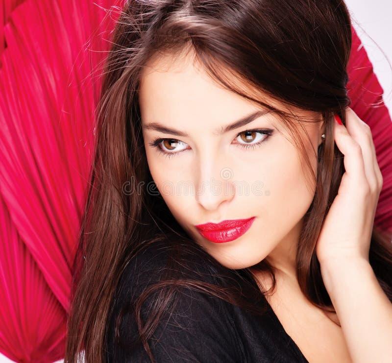 Frau vor roten Gebläsen stockfotos