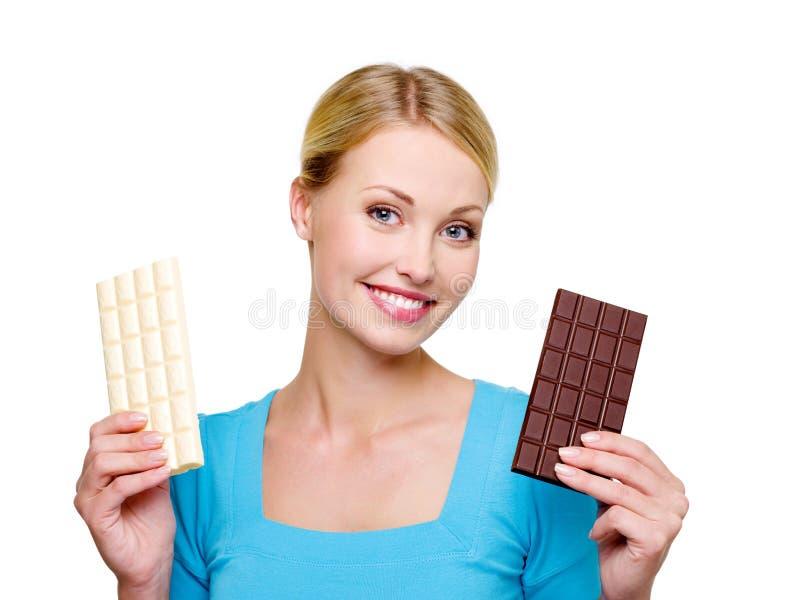 Frau wählen von der süßen und Bitterschokolade stockbilder