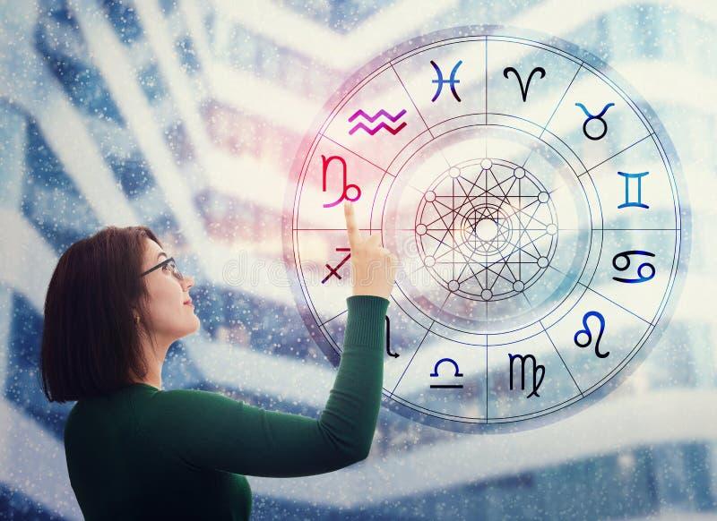 Frau wählt aus dem astrologischen Rad ein Tierzeichen, um die zukünftigen Vorhersagen zu finden Vertrauen in das Horoskop, Beratu lizenzfreies stockfoto