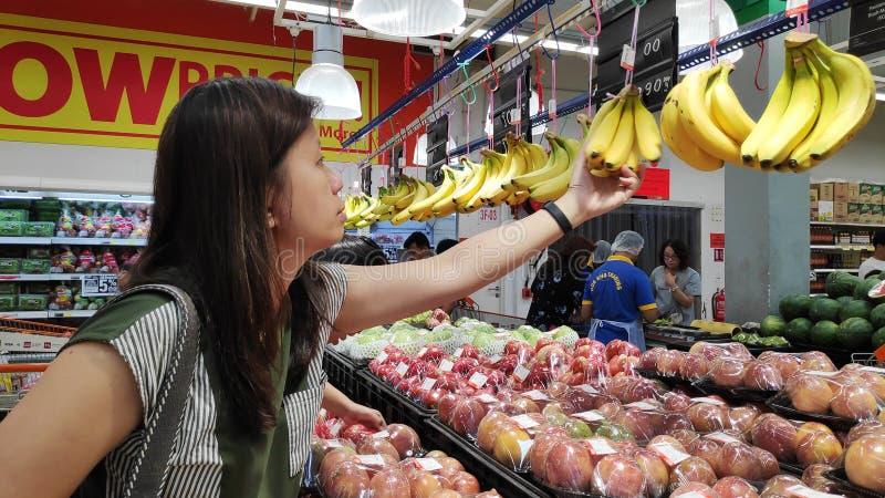 Frau wählt Früchte an einem Markt in Johor Bahru Malaysia lizenzfreie stockbilder