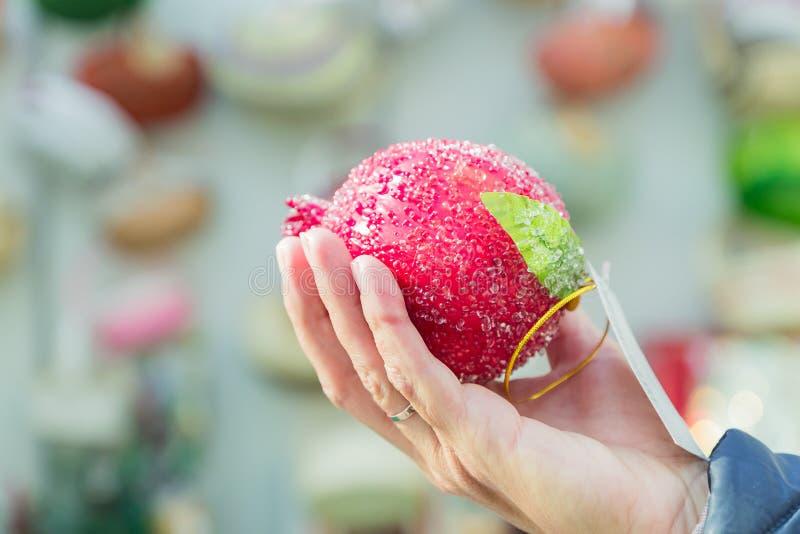 Frau wählt Weihnachtsdekoration für einen Messeurlaub Schönes handgefertigtes Pomegranat in der weiblichen Hand lizenzfreies stockfoto