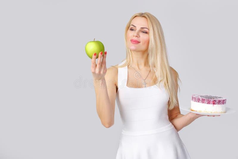 Frau wählt zwischen Kuchen und Apfel stockfotos