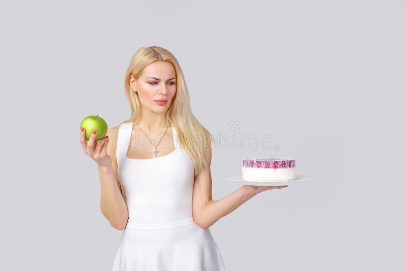 Frau wählt zwischen Kuchen und Apfel stockfotografie