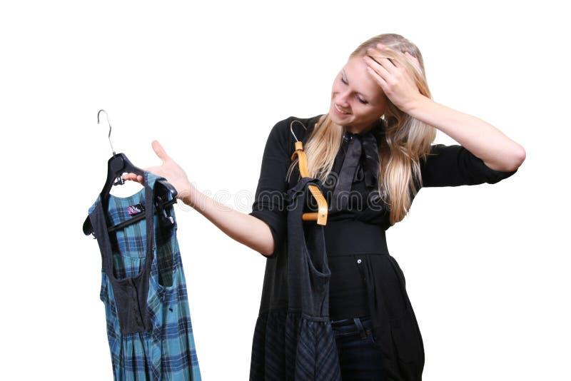 Frau wählt zwischen zwei Kleidern lizenzfreie stockfotos