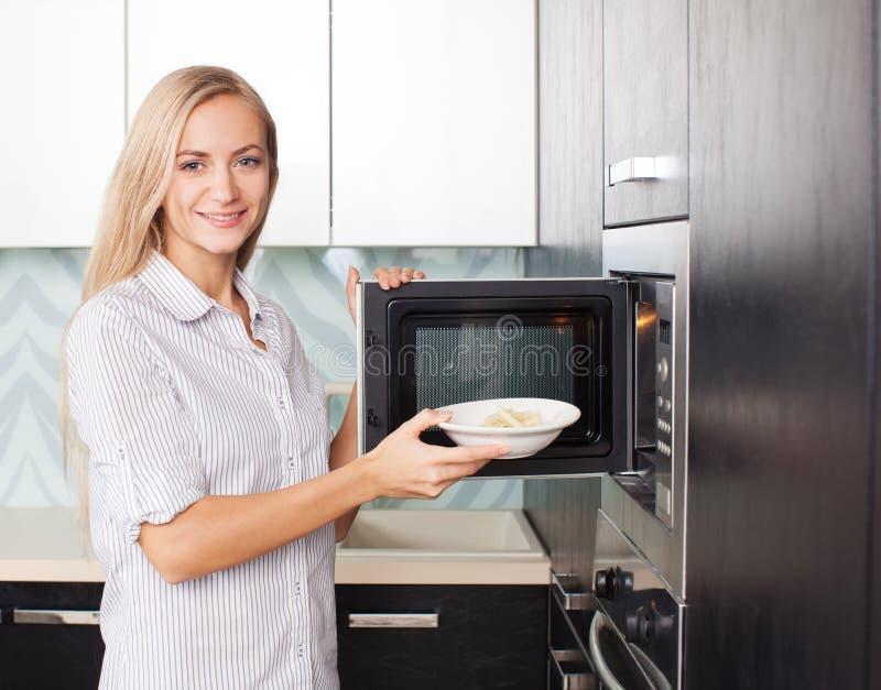 Frau wärmt Nahrung in der Mikrowelle auf lizenzfreie stockbilder