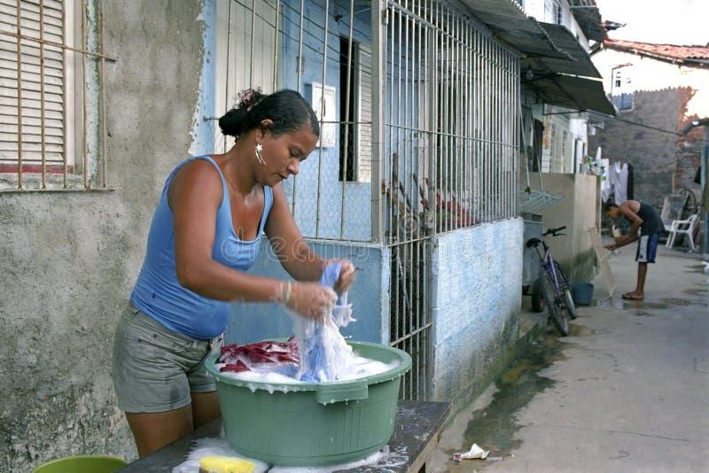 Frau wäscht Kleidung in Brasilien-Elendsviertel in Recife stockbild