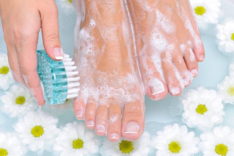 Frau wäscht und säubert ihren Fuß lizenzfreies stockfoto