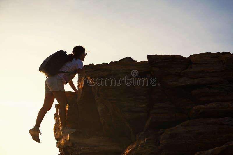 Frau wandernd, klettern Sie, um Hügel bei Sonnenuntergang zu übersteigen lizenzfreie stockfotos