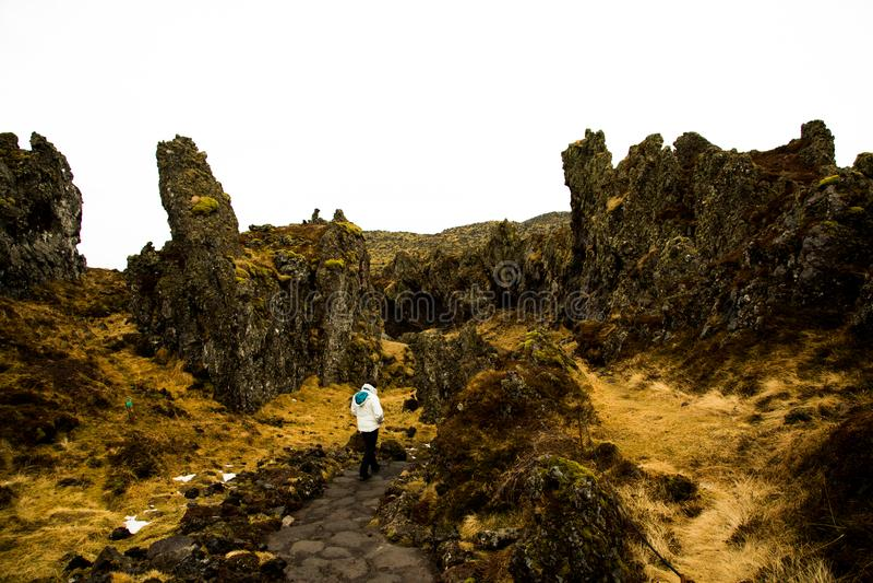Frau wandert durch Lavabildungen in Island lizenzfreie stockfotografie