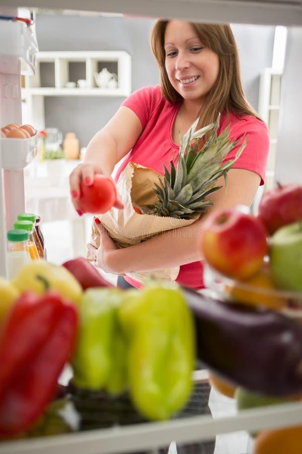 Frau war im Kauf und im vollen Kühlschrank mit gesundem Lebensmittel lizenzfreie stockfotos