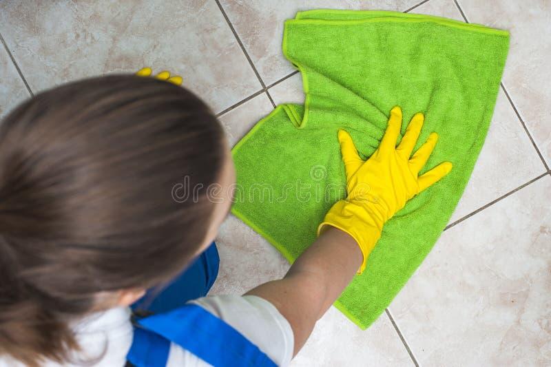 Frau in waschenden Böden der Arbeitskleidung mit grünem Lappen stockfoto