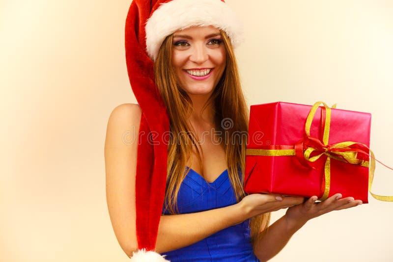 Frau in Weihnachtsmann-Hut hält Geschenkbox Rote Hintergrundnahaufnahme stockfoto