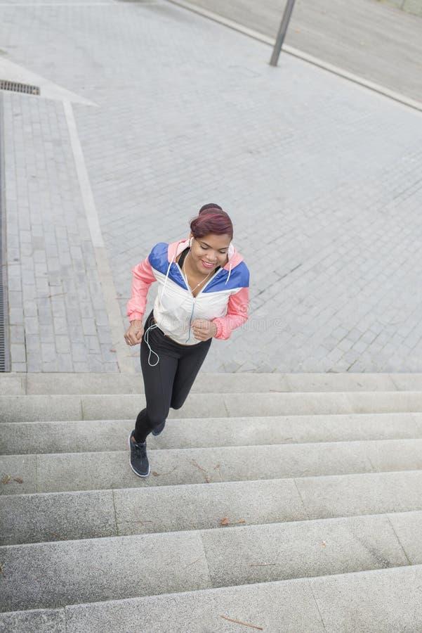 Frau, welche die Übung, rüttelnd auf und ab die Treppe tut lizenzfreies stockfoto