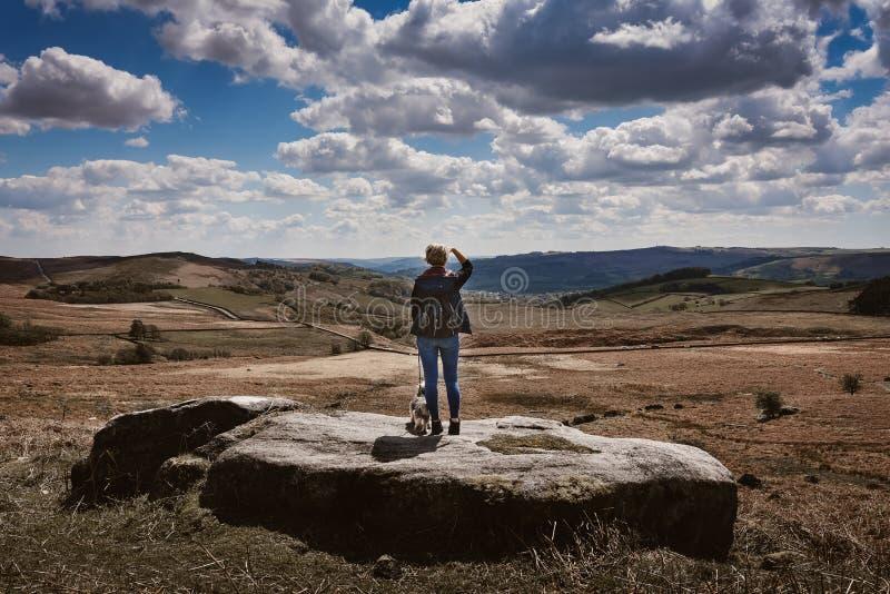 Frau, welche die Ansicht an Derbyshire-Felsen aufpasst stockfotografie