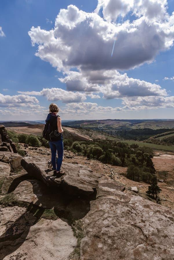 Frau, welche die Ansicht an Derbyshire-Felsen aufpasst lizenzfreie stockfotos