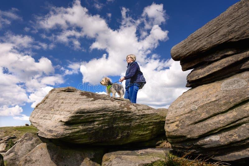 Frau, welche die Ansicht an Derbyshire-Felsen aufpasst lizenzfreie stockbilder