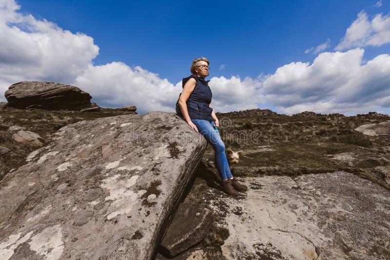 Frau, welche die Ansicht an Derbyshire-Felsen aufpasst lizenzfreies stockfoto