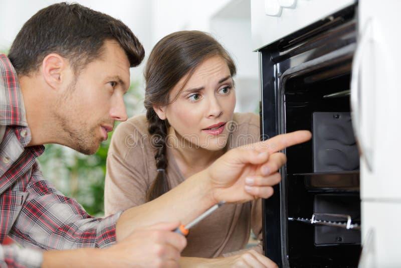 Frau, welche die Arbeitskraft repariert Ofen betrachtet lizenzfreie stockfotos