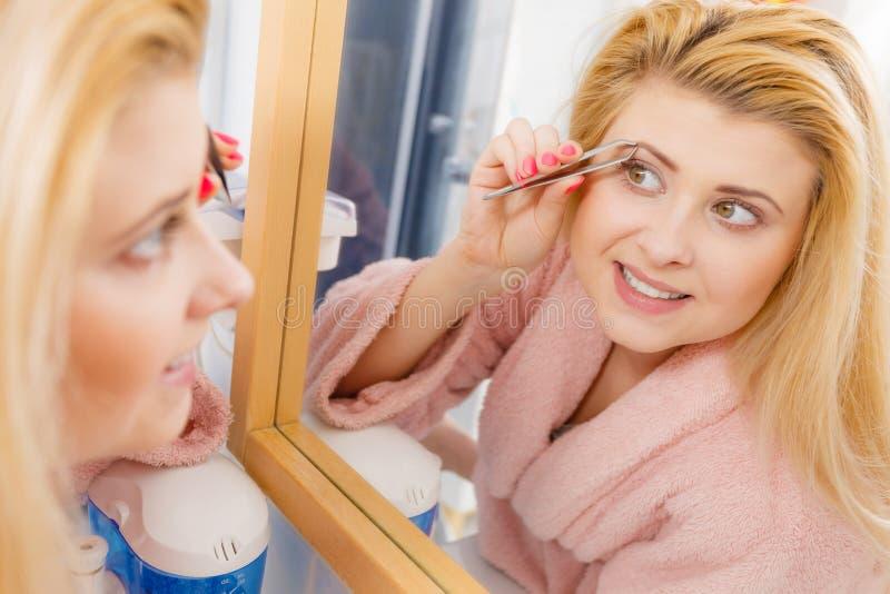 Frau, welche die Augenbrauen enthaaren mit Pinzette auszupft lizenzfreie stockbilder