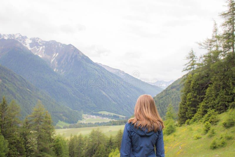 Frau, welche die Berge in Österreich betrachtet stockfotos