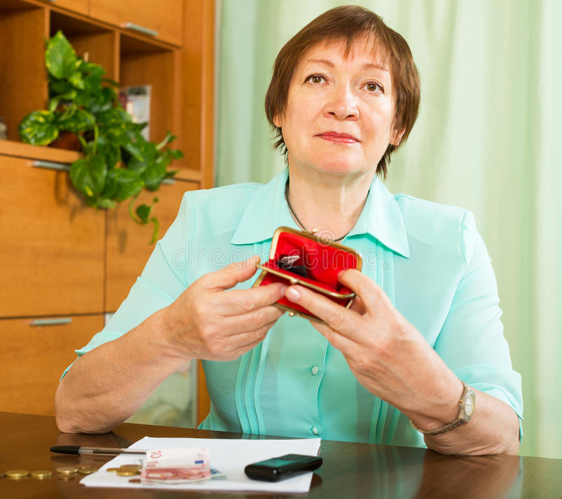 Frau, welche die betroffene Zählung des Geldes schaut stockbild