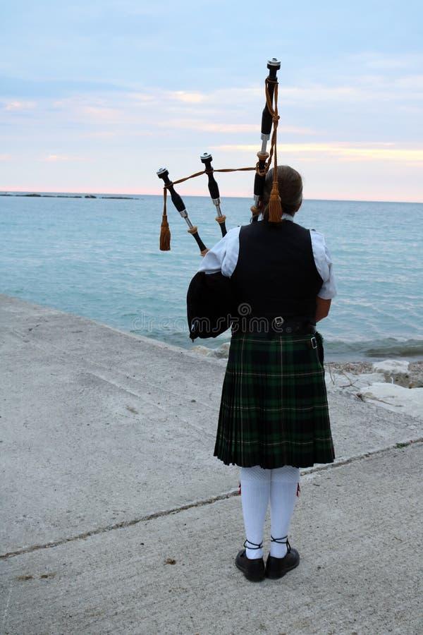Frau, welche die Dudelsäcke beim Huronsee in Kincardine spielt lizenzfreie stockfotografie