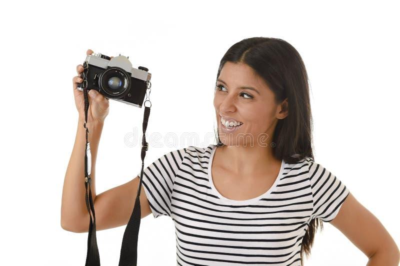 Frau, welche die Fotos aufwerfen das Lächeln glücklich unter Verwendung der kühlen Retro- und Weinlesefotokamera macht stockbild