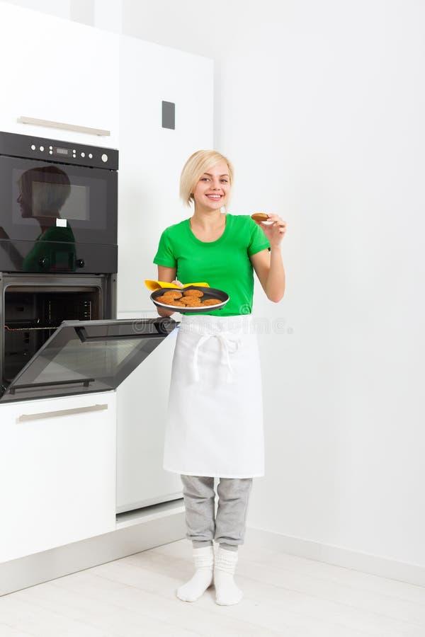 Frau, welche die Geschmackplätzchen backen Ofenbehälter kocht lizenzfreie stockbilder