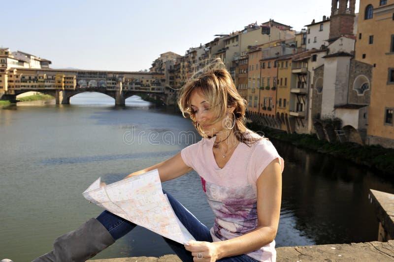 Frau, welche die Karte schaut stockfoto