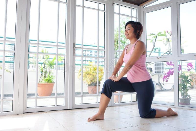Frau, welche die Kniesehne ausdehnt Übung tut stockbilder