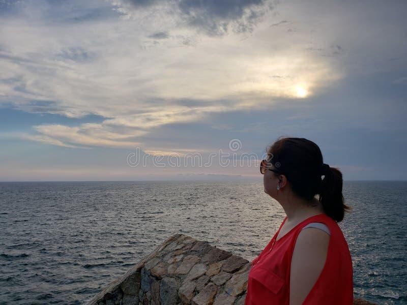 Frau, welche die Landschaft in einem tropischen Platz bei Sonnenuntergang betrachtet lizenzfreies stockbild