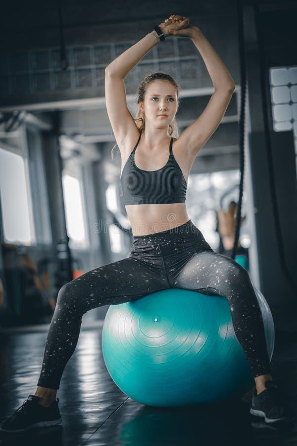 Frau, welche die Muskeln ausdehnt und nach Übung sich entspannt lizenzfreie stockfotos
