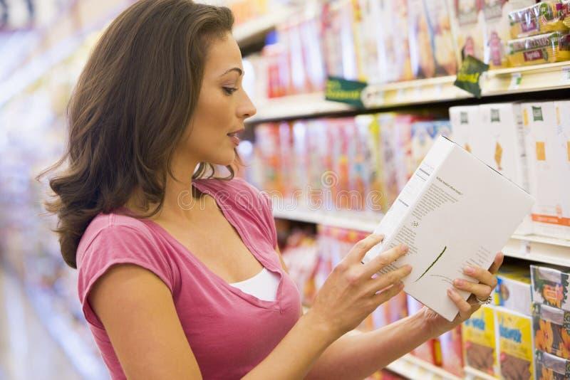 Frau, welche die Nahrungsmittelkennzeichnung überprüft stockfotografie
