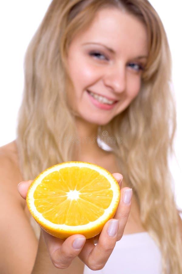 Frau, welche die Orange anhält stockbild