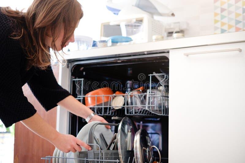 Frau, welche die Spülmaschine öffnet stockbild