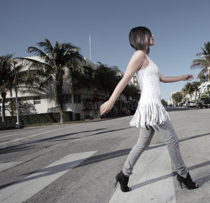 Frau, welche die Straße kreuzt stockfoto