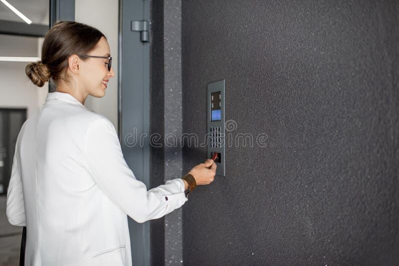 Frau, welche die Tür mit keychain öffnet stockfotos