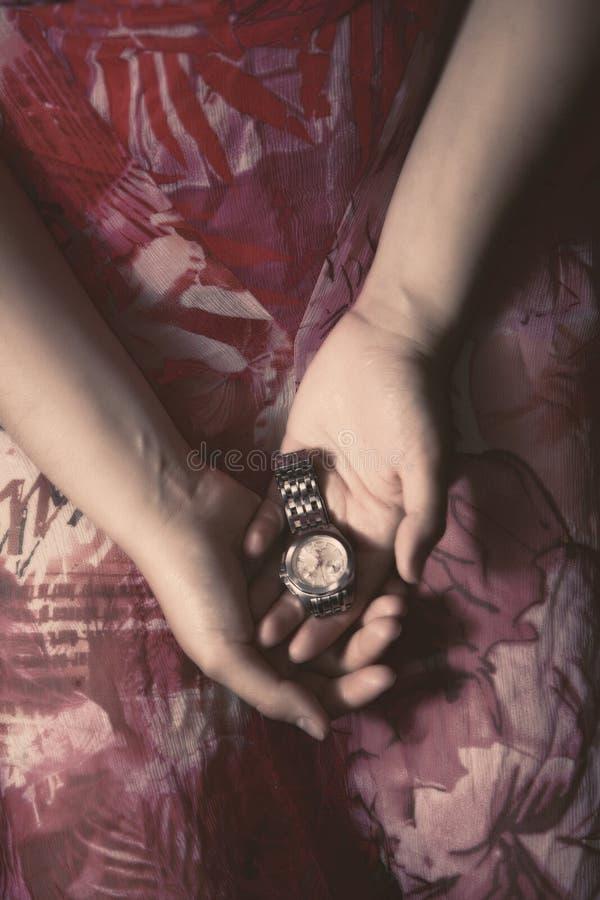 Frau, welche die Uhr des Mannes hält lizenzfreies stockfoto