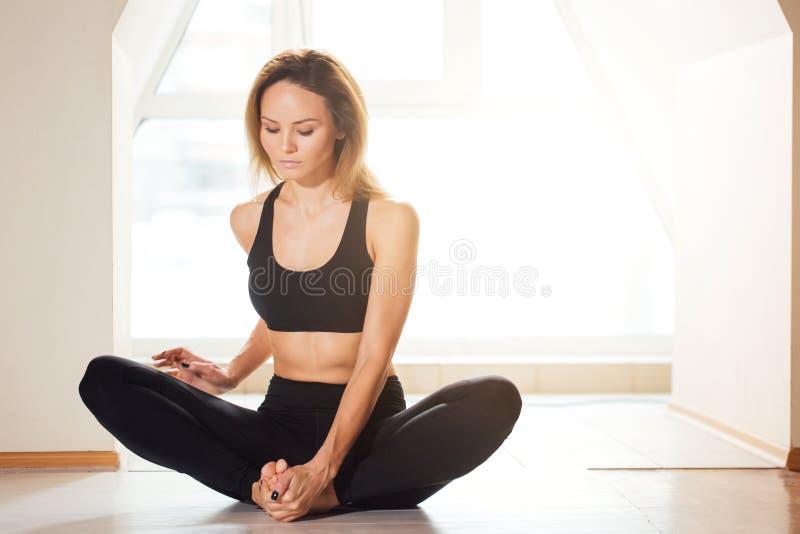Frau, welche die Yogaübung, sitzend in baddha konasana, Schmetterlingshaltung tut lizenzfreie stockbilder