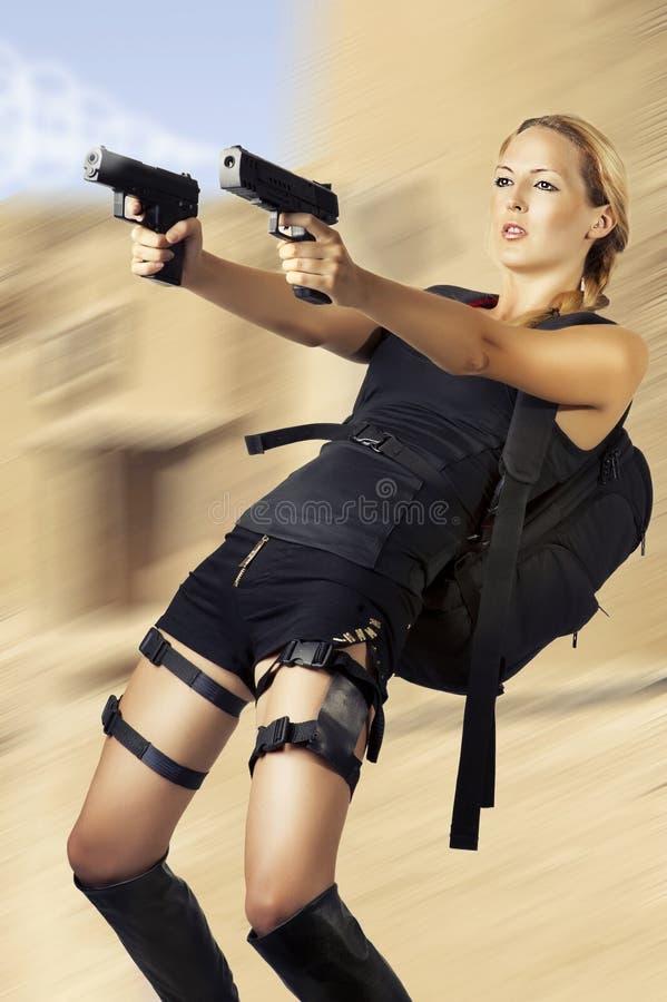 Frau, welche die zwei Handgewehr anhält stockfotografie
